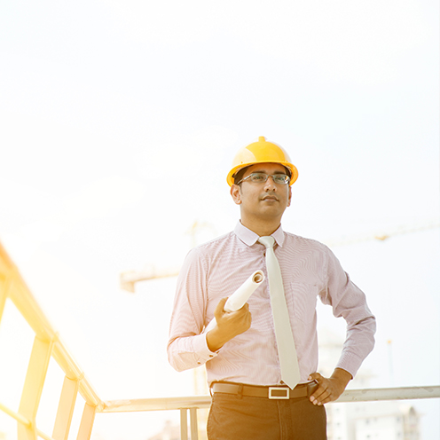 A man in a suit holding blueprints and wearing a helmet